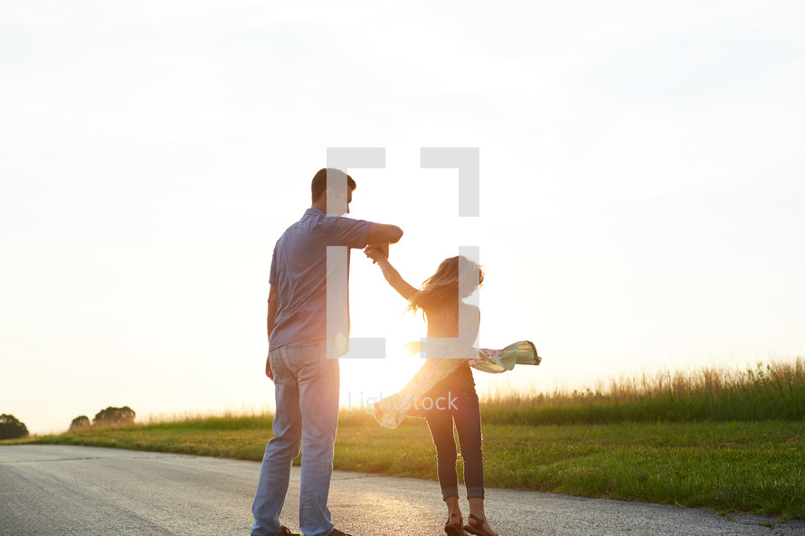 a father dancing with his daughter outdoors
