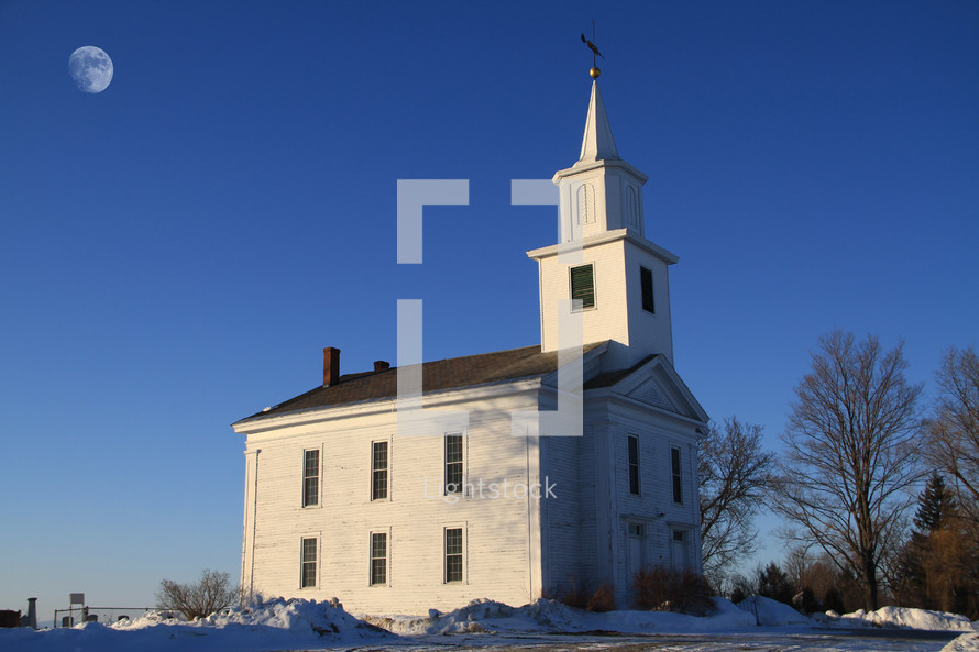 white church and steeple surrounded by snow and a full moon overhead