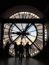 silhouettes of people and a clock tower