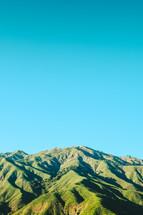 green mountain under a blue sky