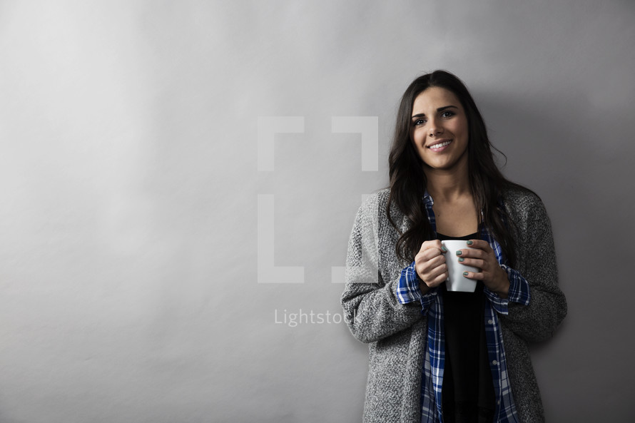 a young woman holding a coffee mug and smiling against a blank wall.