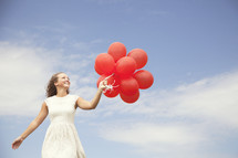 teenage girl walking and holding red balloons