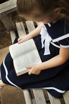 Girl sitting on a park bench reading the Bible.