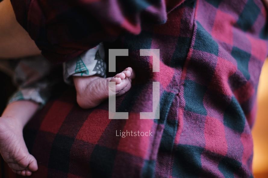 newborn baby feet against a plaid shirt