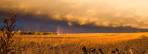 weather front over a field and a rainbow