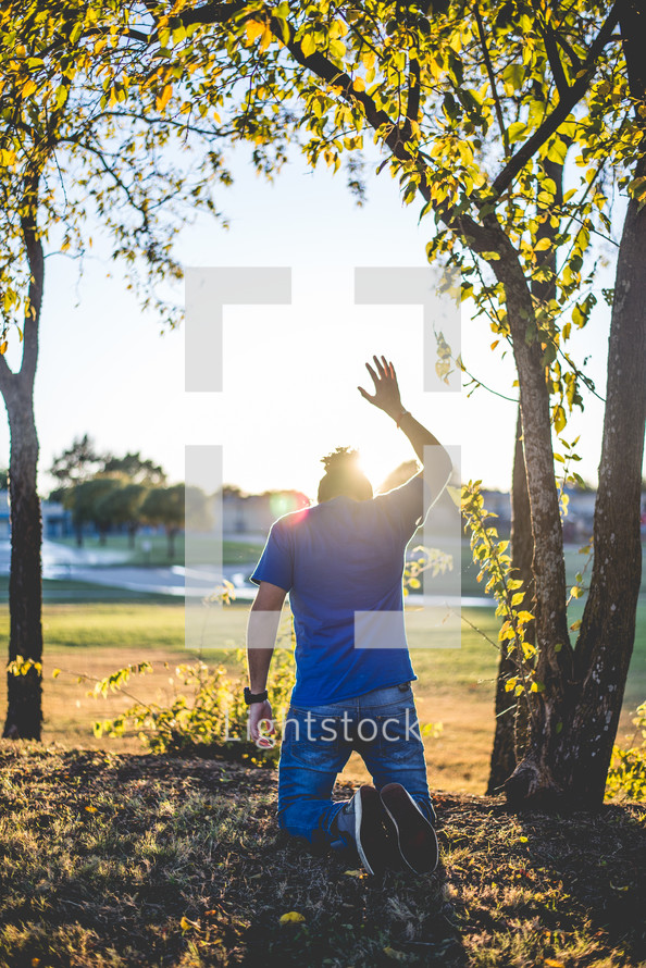 man kneeling outdoors with hand raised