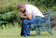 man with tattooed hands praying sitting on a park bench
