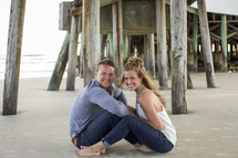 a couple sitting on a beach under a pier