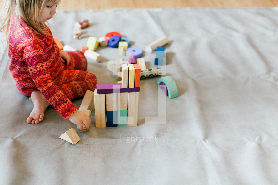 a toddler girl playing with building blocks