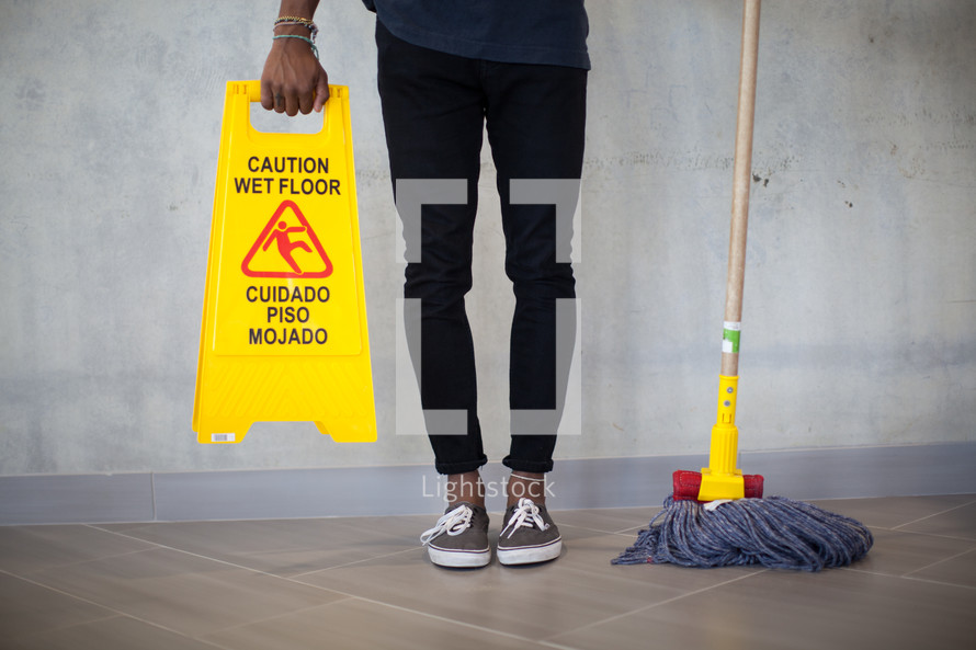 woman holding a mop and wet floor sign
