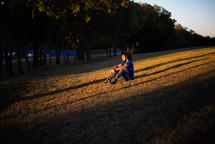 a man sitting on a grassy hill