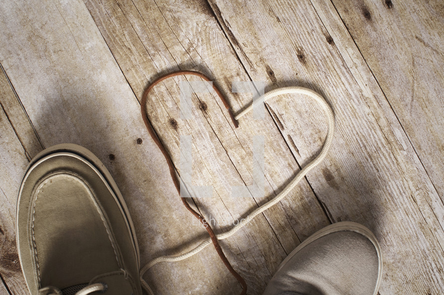 brown and white shoes laces together in the shape of a heart