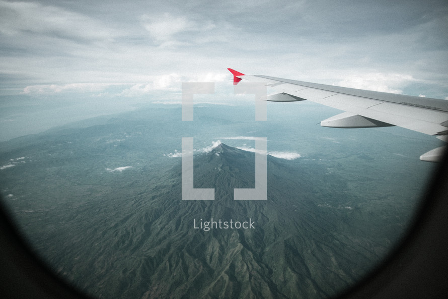 wing of a plane flying over mountains