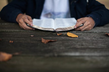 teen boy reading a Bible at a picnic table