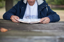 torso of a teen boy reading a Bible