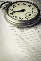 stop watch on the pages of a Bible