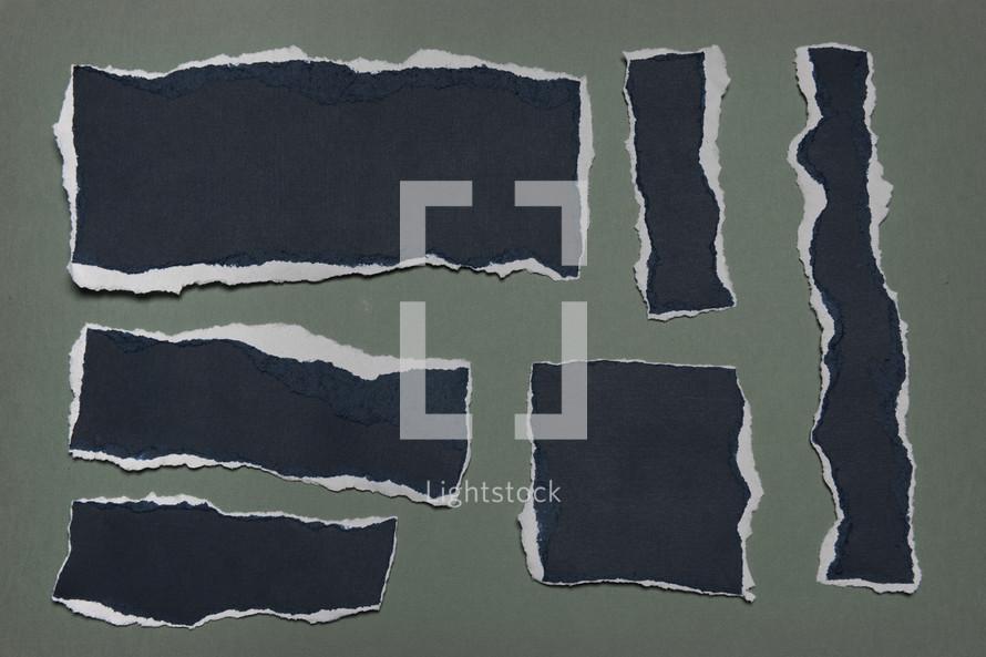 Black shapes beneath torn gray paper.