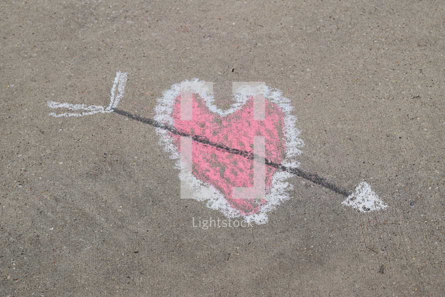 cupid's arrow through a heart in sidewalk chalk
