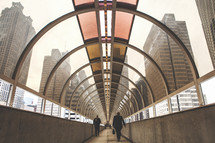 Skylight walkway between buildings in a city with men walking across