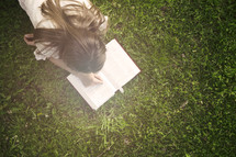 Teenage girl laying down and reading Bible in a field of green grass.