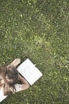 girl reading a Bible in the green grass