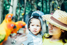 a mother and daughter watching parrots at the zoo