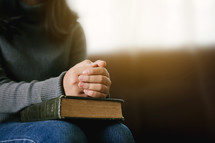 a woman praying with a Bible in her lap