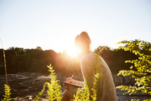 a woman journaling outdoors at sunset