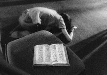 kneeling in prayer with a Bible in a chair
