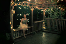 Woman sitting in a lighted gazebo at night.