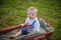 toddler boy in a red wagon