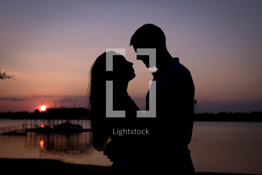 silhouette of a couple in love standing by a lake at dusk