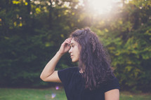 a woman touching her hair standing outdoors