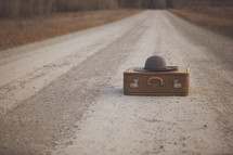 a gravel road with suitcase and hat