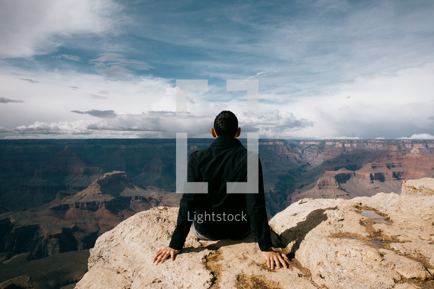 man sitting at the edge of a canyon landscape