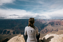 woman sitting at the edge of a canyon landscape