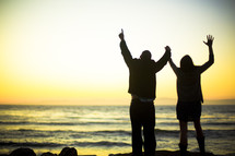 couple with raised arms on a beach - worship to God