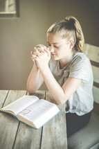 a girl reading a Bible and praying