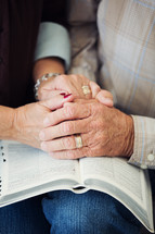 an elderly couple holding hands and praying over the pages of a Bible.