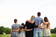a family standing with arms around each other