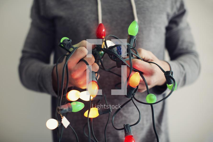 a man holding tangled Christmas lights