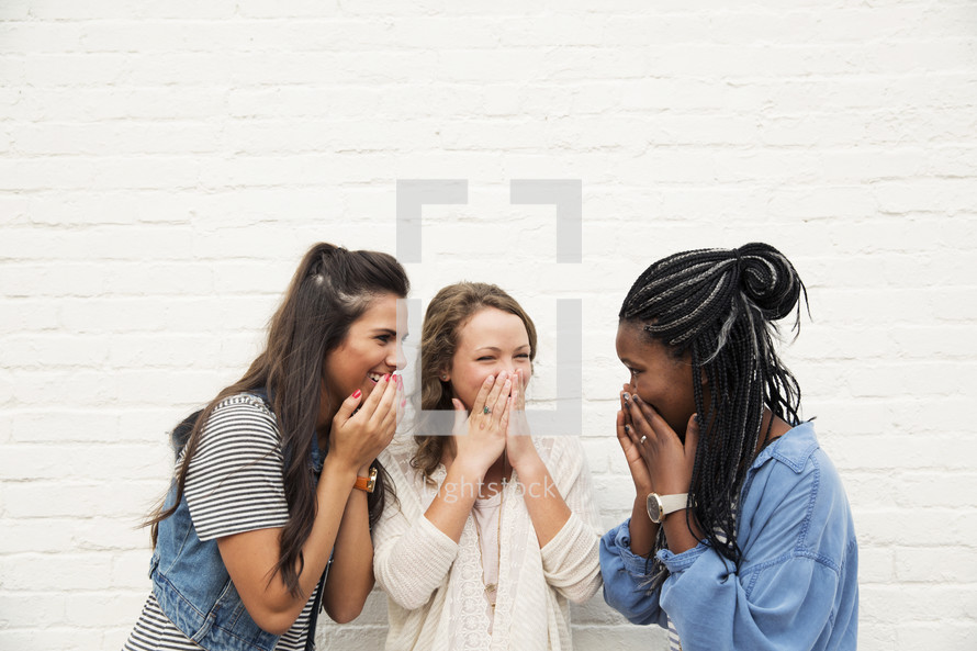 Friends laughing together standing against a white brick wall.
