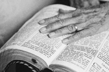An elderly woman's hand on an open Bible.