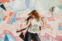 A young woman dancing in front of a colorful painted wall.
