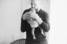 Father holds his infant child.
