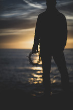 silhouette of a man standing on a shore holding a crown of thorns