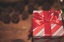 A red and white gift box with pine cones