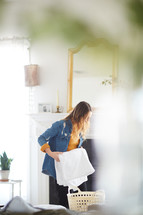 a woman folding towels in her home.
