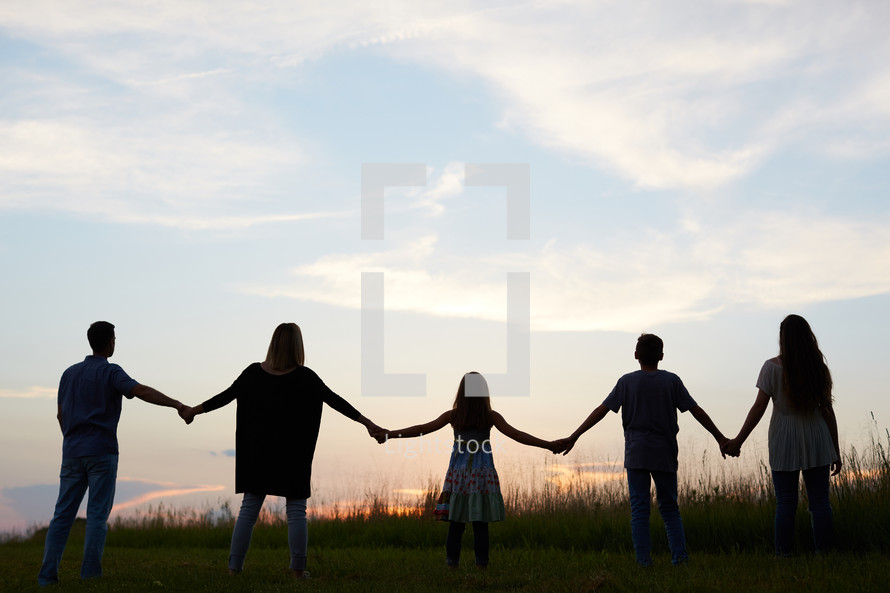 a family standing holding hands