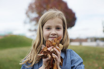 a girl holding fall leaves